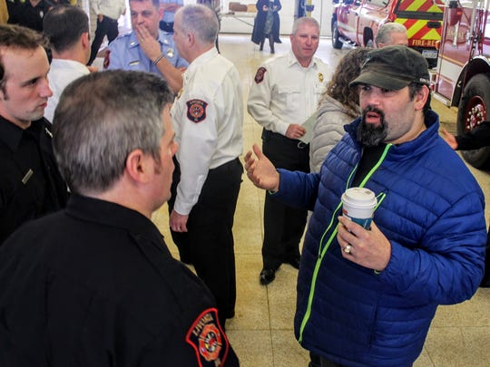 Livonia resident Roland Gebnar speaks to firefighters Nathan Lee and Mike Authier at Livonia fire station 1.