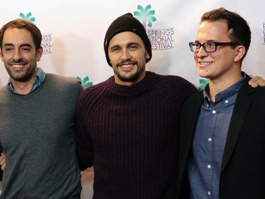 "Actor James Franco (center) stops on the red carpet for a large group photo with some of the co-directors of ""Don Quixote: the Ingenious Gentleman of La Mancha"" including Will Lowell (left) and Austin Kolodney (right) on Wednesday, January 7, 2015 during the Palm Springs International Film Festival in Palm Springs, Calif."