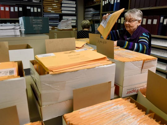 Millie Blake processes absentee ballots in the safe of the Minnehaha County Auditor's office in the Administration Building in downtown Sioux Falls on Friday, Oct. 28, 2016.