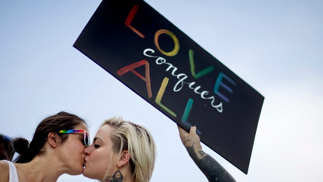 Adriana Kelley, right, kisses Tiffany Findley, both of Orlando, as they stand with supporters outside the visitation for Pulse nightclub shooting victim Javier Jorge-Reyes Wednesday, June 15, 2016, in Orlando, Fla. (AP Photo/David Goldman)