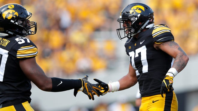 FILE - In this Sept. 1, 2018, file photo, Iowa defensive back Amani Hooker, right, celebrates with teammate Chauncey Golston after intercepting a pass during the first half of an NCAA college football game against Northern Illinois in Iowa City, Iowa. Hooker was good a year ago, making 56 tackles, but he's been an indispensable member of Iowa's young but talented back seven as a junior.  (AP Photo/Charlie Neibergall,File)