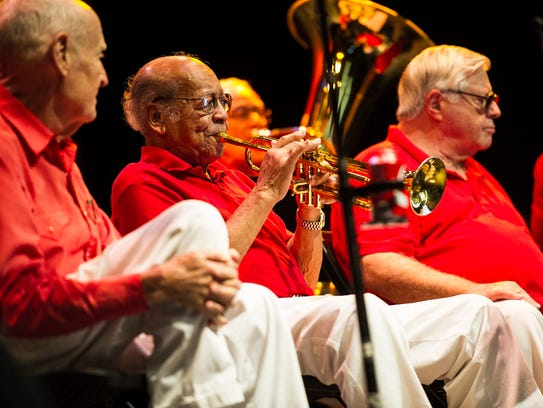 Renald Richard (center) plays the trumpet during a