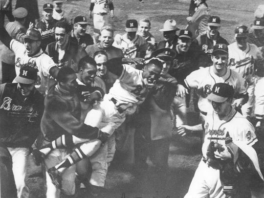 Hank Aaron's teammates hoist him in the air after his 11th home run beats the St. Louis Cardinals and clinches the 1957 National League pennant at County Stadium on Sept. 23, 1957.