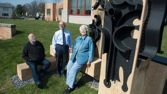 Cherry Hill residents - David Ascalon (L to R), who redesigned and istalled the sculpture, Fred Adelson, Prof. of Art History at Rowan and art activist Sally Callaghan and by the George Greenamyer metal sculpture from the former Malcolm Wells library in Cherry Hill which has now been reinstalled on the front lawn of the Cherry Hill library. Thursday, March 24, 2016.