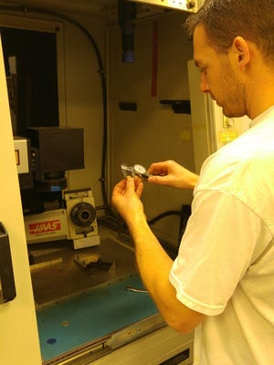 An aScribe Laser employee works at the company's facility.