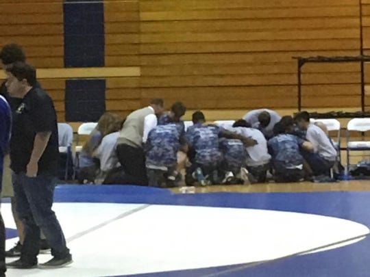 Wrestlers kneel in prayer while Donovan Catholic's Brandon Gonzalez is attended to by coaches, trainers and EMTs. Gonzalez was revived by a defibrillator following his match at Lakewood High School.