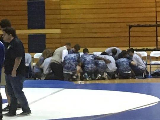 Wrestlers kneel in prayer while Donovan Catholic's