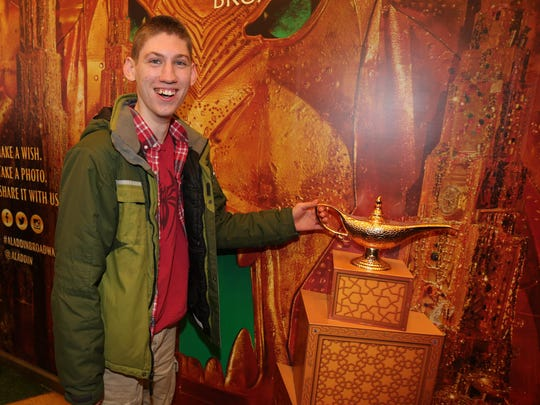"""Raymond Pomeroy, 17, from South Salem, giggles as he is able to touch """"the magic lamp"""" in the outer lobby of Broadway's New Amsterdam Theatre, where he and his family attended an autism-friendly performance of """"Aladdin."""""""