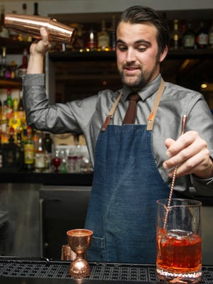 In this Thursday, Sept. 28, 2017, photograph, Zach Bowersock mixes a cocktail at the Chef's Club in Aspen, Colo. Bowersock is trying to make a difference in the world one cocktail at a time. (Anna Stonehouse/The Aspen Times via AP)