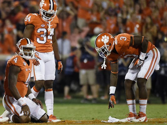 Clemson wide receiver Artavis Scott (3) picks up a towel as teammates Deshaun Watson (4) and Clemson wide receiver Ray-Ray McCloud (34) react to a fumble during the first half of an NCAA college football game against Louisville on Saturday, Oct. 1, 2016, in Clemson, S.C. (AP Photo/Rainier Ehrhardt)