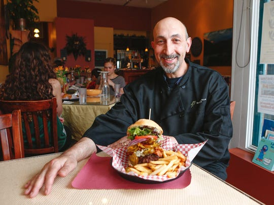 Bob Nevelus, cafe chef-owner, with his Blazin' Blue Cheeseburger.