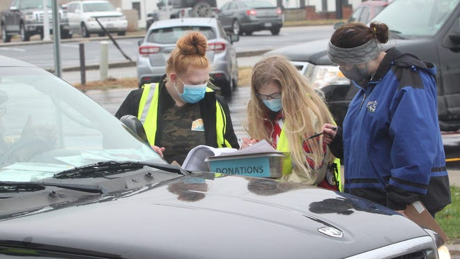 Kayla Massie, right, is joined by Moberly High School Astra Club members Maddie Taylor, left, and Anna Rivera as they review a document to verify if a motorist's name is shown on a list of persons who  made an advance reservation to receive a free meal Wednesday at the annual Moberly Community Goodwill Thanksgiving Dinner drive-thru event in Missouri. In lieu of its traditional buffet-style sit-down dinner, the coronavirus pandemic forced organizers to change its format and require persons to meet a Nov. 17 deadline to reserve a meal for pick up.