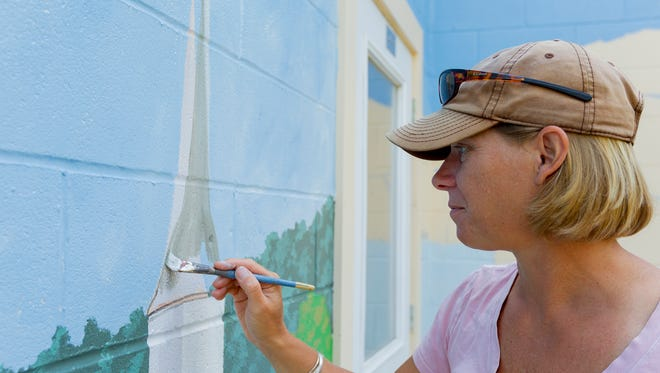 Mary Beth Ihnken, of Brooktondale, creates a mural showing the history of Brooktondale on the back of the Brooktondale Community Center.