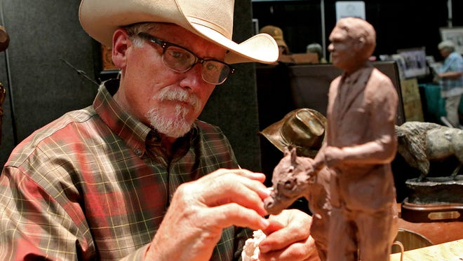 Artist John Rule works on a model for a sculpture he's working on to present to a group in Midwest City, Okla., while in his booth for Cowboy True Saturday afternoon in the J.S. Bridwell Agricultural Center.