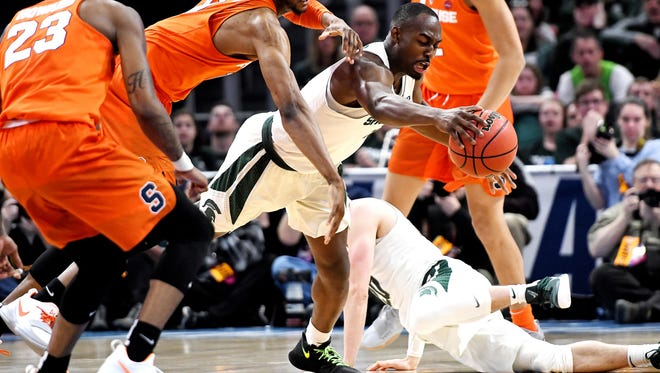 Michigan State's Joshua Langford, right, dives for the ball along with Syracuse's Oshae Brissett, left, during the first half on Sunday, March 18, 2018, at the Little Caesars Arena in Detroit.