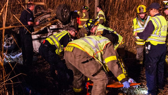 First responders work on removing one man from a vehicle after a rollover crash in Chili early Saturday morning.