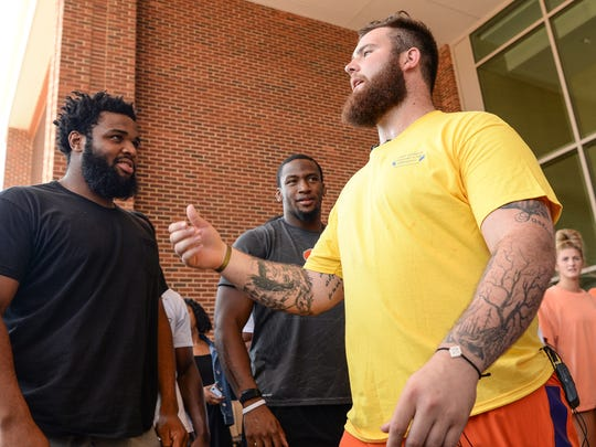 "Clemson football player Christian Wilkins, left, and Clelin Ferrell listen to Sean Pollard speak during the ""All Off for Cancer"" event at the Allen N. Reeves Football Complex in Clemson on Wednesday. The event is in conjunction with the Clement's Kindness Fund for Children and raises money for pediatric cancer research. Members of the football team and other student-athletes in other sports had their heads shaved by children fighting cancer."