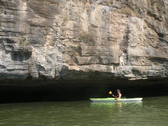 Betty Glenn paddlers her kayak before a cliff along