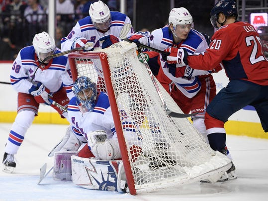 New York Rangers goaltender Henrik Lundqvist (30), of Sweden, looks at the net being tilted forward as Washington Capitals center Lars Eller (20) and Rangers center Lias Andersson (50) and defenseman Brady Skjei (76) work behind the net during the second period of an NHL hockey game Wednesday, March 28, 2018, in Washington. (AP Photo/Nick Wass)