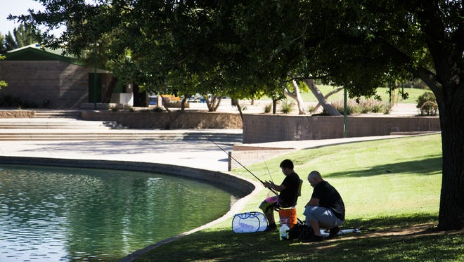 Andrew Whitehead (left) and Stephen Carrera fish in the shade of a tree as temperatures continue to rise in the triple digits at Dobson Ranch Park in Chandler on June 5, 2017.