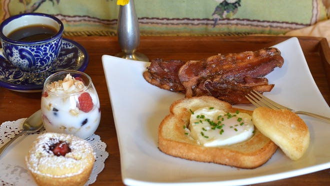 Yogurt parfait, cornmeal muffin, bacon and a heart-shaped egg in bread add up to a special breakfast in bed for mom.
