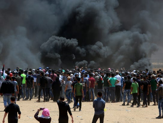Palestinian protesters burn tires near the Israeli
