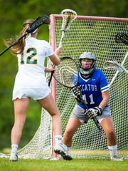 Stephen Decatur goalkeeper Rachel Florek (11) prepares for a shot by Queen Anne's midfielder Abby Folker (12) in the Bayside Championship on Tuesday, May 10 at Queen Anne's High School in Centreville.