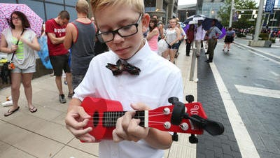 Ty Jones, 15, St. Louis, Mo., practices on his ukelele on Georgia Street in Downtown Indianapolis as he waits to audition for American Idol on Thursday morning, June 25, 2015.