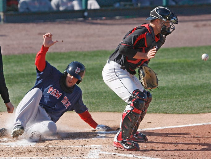 Pawtucket's Alex Hassan slides safely home as the relay throw bounces in to Red Wings catcher Dan Rohlfing during the fourth inning of their game Wednesday, April 16, 2014.