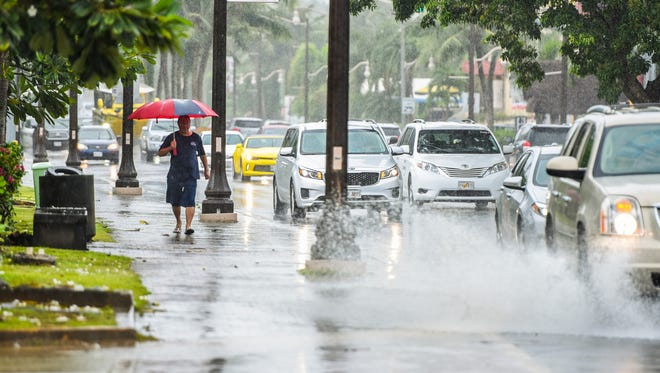 A pedestrian tries to avoid getting splashed by passing vehicle traveling on San Vitores Road during a downpour in Tumon on Tuesday, Oct. 17, 2017.