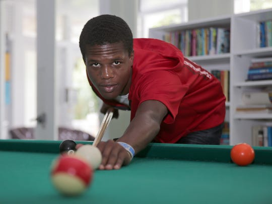 Kris Pullock, a homeless student at Miami Bridge Youth & Family Services, plays pool during a break on Wednesday Sept. 14, 2016 in Miami.