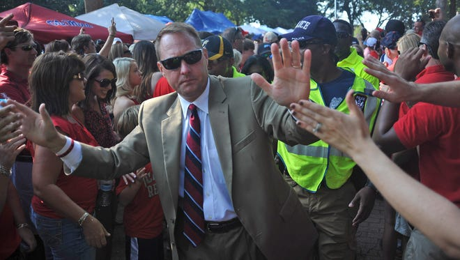 Mississippi coach Hugh Freeze greets fans as the team walks through the Grove before an NCAA college football game against Missouri State in Oxford, Miss. on Saturday, Sept. 7, 2013.