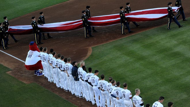 The Reno Aces line up for the singing of the National Anthem during opening day at Aces Ballpark in Reno in April 17, 2015.