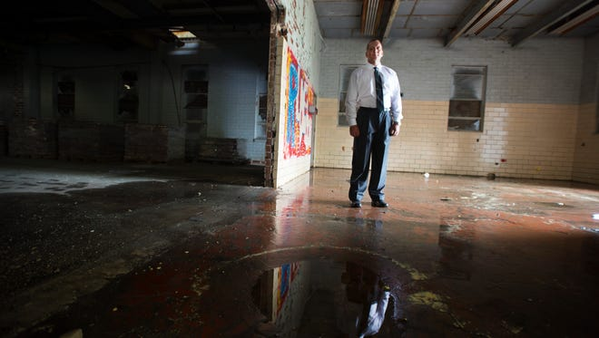 Erin Roussey, president of US Building Innovations, stands inside an old school in Newry he is redeveloping for his company on Friday, April 1, 2016.