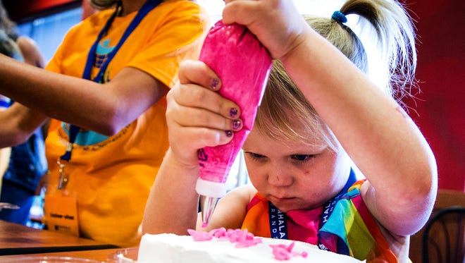 At Take Your Kids to Work Day at the Cold Stone Creamery headquarters in Scottsdale, Klaire Stanley, 6, decorates a cake, Thursday, April 28, 2016.