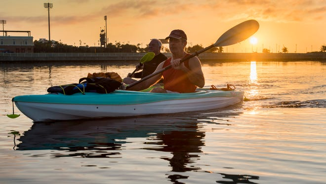 Jerry Holzworth, left, and Dan Lindemann kayak to Bruce Beach as the sun rises in Pensacola on Tuesday, November 7, 2017.  A fish hatchery is proposed to be built on the Bruce Beach property.