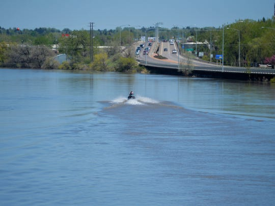 A jet skier motors down the Sun River towards  the confluence with the Missouri River above Broadwater Bay on Tuesday afternoon.  The Warden Bridge can be seen in the background.