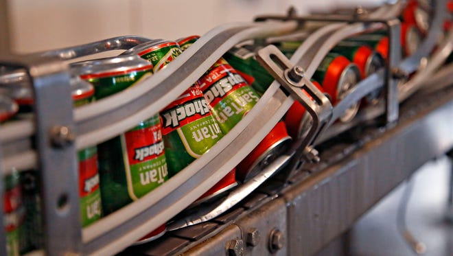 Freshly canned beer runs through the canning line and is dated at the SanTan Brewing Company in Chandler.