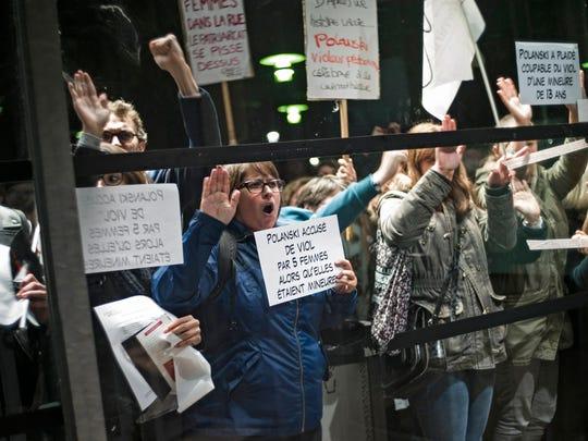 Protesters shout slogans outside La Cinematheque against