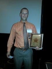 Indiana State Police Trooper Tyler Stinson holding the Five Star Valor Award from the Indiana Sheriff's Association.