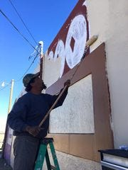A fresh layer of paint is applied to the building that used to house a pool hall but which is slated to become the resource center for the new Carlsbad Community of Hope, a tent city that could house up to 50 of Carlsbad's homeless