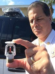Estero Fire Marshall Phillip Green shows the sprinkler head that the district wanted to make mandatory in one-and two-family homes. The requirement was repealed this month in the face of a legal challenger.