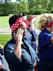 Canton resident Danielle Helms salutes as she and 15 other Rosie the Riveters practice for the Thanksgiving Parade in Detroit.