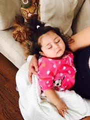 Melanie Diaz, 9 months, sleeps in her mother's arms a day after Long Branch police Officer Omar Akel saved her from choking.