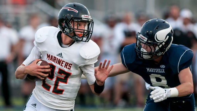 Marine City senior Kohl Sobol runs the ball as Marysville senior Jake Lasher puts on pressure during a football game Friday, September 16, 2016 at Marysville High School.