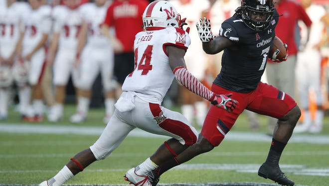 Cincinnati Bearcats running back Tion Green (7) stiff-arms Miami RedHawks defensive back Tony Reid (14) in the fourth quarter during the college football game between MU and the Cincinnati Bearcats , Saturday, Sept. 24, 2016, at Nippert Stadium in Cincinnati.