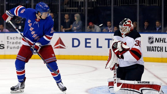 New Jersey Devils goalie Cory Schneider (35) makes a save in front of New York Rangers left wing Jimmy Vesey (26) during the second period of an NHL preseason hockey game Wednesday, Sept. 20, 2017, in New York. (AP Photo/Adam Hunger)