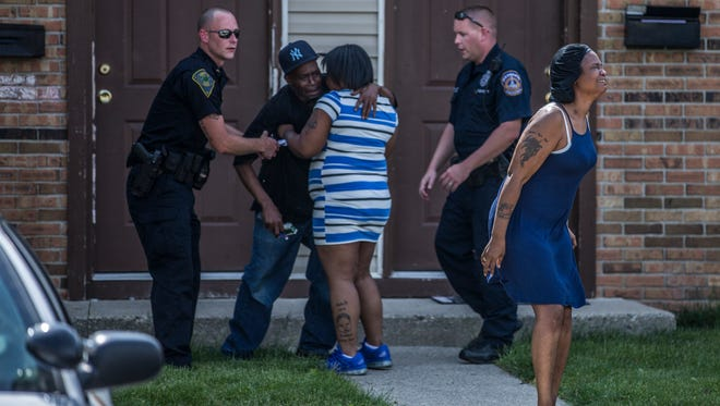 A woman cries out as a man collapses behind her at the scene where a 9-year-old boy was fatally shot May 27 in Cumberland.