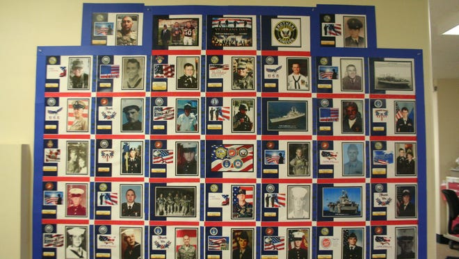 Purchasing aide Eileen Smith and purchasing supervisor Kathy Ogden of South Lyon Medical Center recently designed a wall display of photos from families who have members who have served in the U.S. military and the Royal Canadian Army.