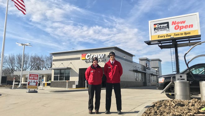 Two Crew Carwash workers stand in front of the Muncie store.
